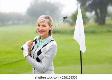 Excited lady golfer standing on a foggy day at the golf course