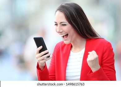 Excited lady in red celebrating good news checking smart phone on line content in the street