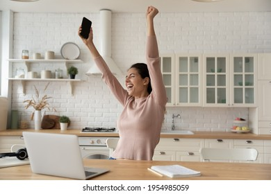 Excited latina woman freelancer raise hands up hold phone scream hooray in delight celebrate finish work on difficult project. Euphoric young lady remote employee meet deadline with all the work done