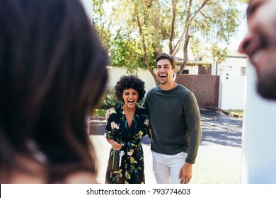 Excited and laughing guests couple coming for housewarming party. Man and woman with wine bottle at the door being welcomed by friends at their new home.