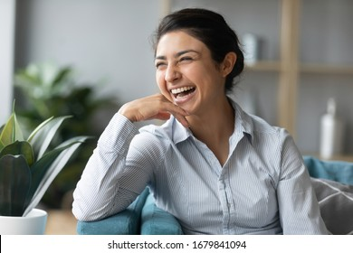 Excited laughing Indian woman sitting on cozy couch, dreaming about good future, looking to aside, happy smiling young female enjoying leisure time at home, having fun, relaxing on sofa