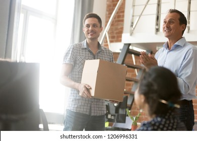 Excited leader boss introducing new employee holding box on first day at work, friendly ceo and team welcoming just hired member newcomer getting acquainted with male coworker, introduction concept