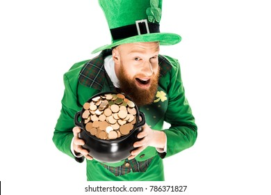 excited leprechaun in green suit and hat holding pot of gold, isolated on white