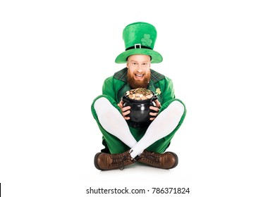 excited leprechaun in green suit holding pot of gold, isolated on white