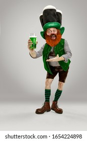 Excited leprechaun in green suit with red beard enjoying green beer pint on white background. Funny portrait of man ready to party. Saint Patrick day, human emotions, celebration, traditional holidays