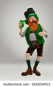 Excited leprechaun in green suit with red beard holding green beer pint on white background. Funny portrait of man ready to party. Saint Patrick day, human emotions, celebration, traditional holidays.