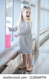Excited little blond-haired girl standing with shopping bag