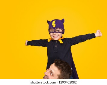 Excited little boy in cute superhero mask smiling and looking at camera while sitting on neck of father on bright yellow background