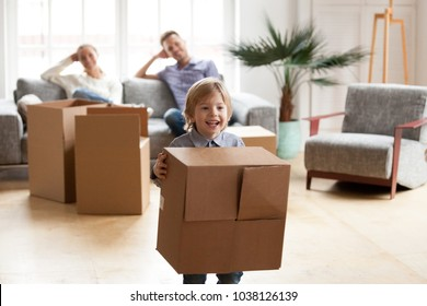 Excited little boy playing with cardboard box on moving day, parents relaxing on sofa while their happy active son enjoying packing relocating into new home, cute kid having fun in modern living room
