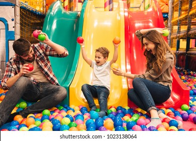 Excited little boy playing on a slide with his parents at entertainment centre