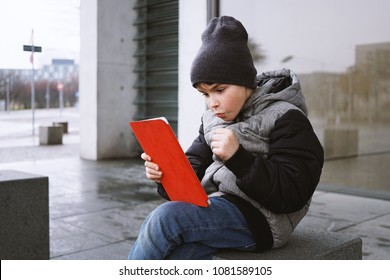 excited little boy playing online game on tablet computer while sitting outside alone on city street in winter, celebrating winning with clenched fist