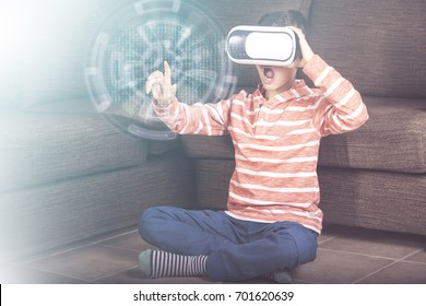 Excited little boy reacts while experiencing virtual reality at home. (Cross processed image with digital effects)