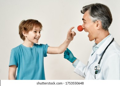 Excited little boy touching clown nose of friendly male pediatrician, isolated over grey background. Doctor and little patient having fun. Healthcare, medicine. Working with kids at clinic