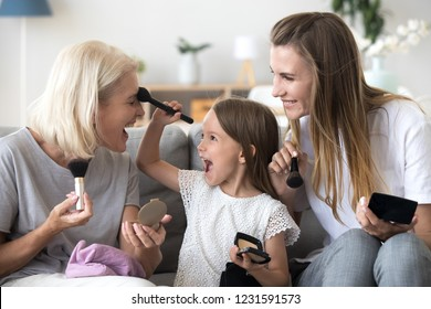Excited little child girl holding brush puts powder on grandmas face doing make-up with mom and grandmother, happy kid granddaughter applying makeup on granny having fun in 3 generations women family