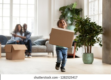 Excited little funny african boy running playing with cardboard box on moving day, black parents and kid son enjoying packing relocating into new home, cute mixed race child having fun in living room