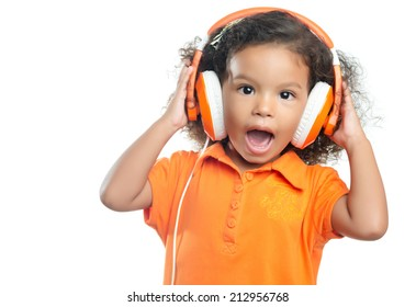 Excited little girl with an afro hairstyle enjoying her music on bright orange headphones (isolated on white)