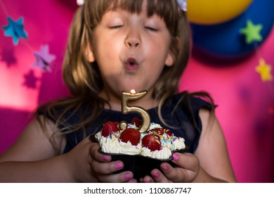 Excited little girl celebrating her birthday and blowing cande on her homemade strawberry cake. Make a wish concept. Anniversary, happiness. Five years old. Selectiv focus
