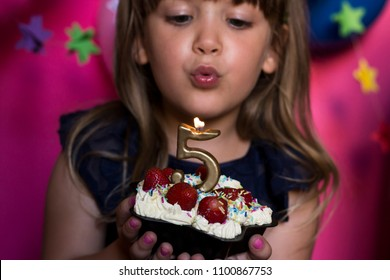 Excited little girl celebrating her birthday and blowing cande on her homemade strawberry cake. Birthday party for children. Make a wish concept. Anniversary, happiness. Five years old. Selectiv focus