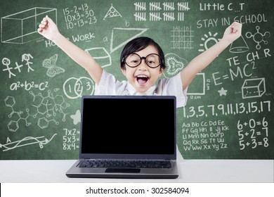 Excited little girl celebrating her achievement and raise hand in the class with empty laptop screen on the table