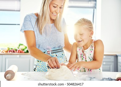 Excited little girl helping her mother make pastry as they knead the dough together at the kitchen counter, high key with sun flare
