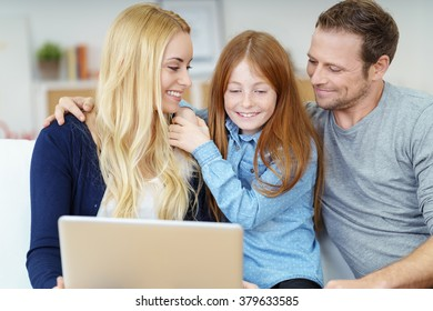 Excited little girl looking at something on a laptop as she sits on a sofa between her parents who are watching her with loving expressions