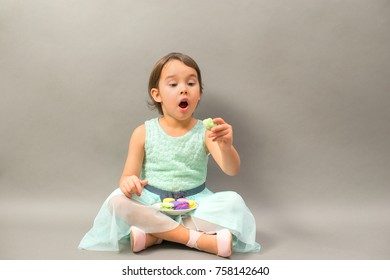excited little girl with a plate full of macaroons