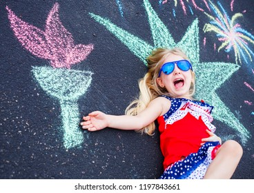 Excited little girl in sunglasses lying on asphalt with painted torch. Cute Caucasian girl wearing stars and stripes dress lying with open mouth. Independence day