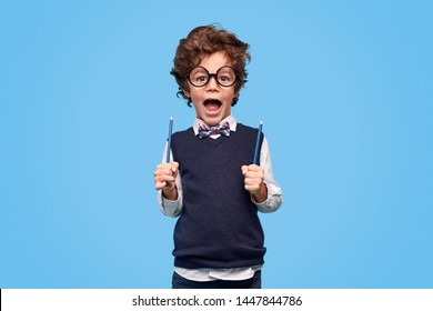 Excited little nerd in round glasses and school uniform screaming and holding two pencils while being ready go back to school against blue background