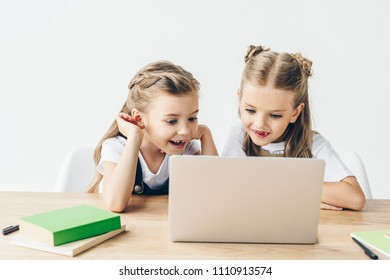 excited little schoolgirls using laptop for studying isolated on white