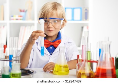 Excited little scientist looking at the foaming liquid in the test-tube