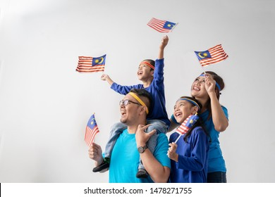 excited malaysian sport fans supporter. asian family with malaysia flag