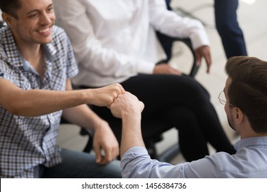 Excited male colleagues give fists bump talking at informal office meeting or brainstorm, smiling men employees greeting at company teambuilding, workers celebrate shared success or goal achievement