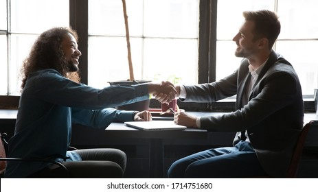 Excited male diverse business partners sit in coffeehouse shake hands getting acquainted, happy man businesspeople handshake greeting or closing deal after successful negotiation in cafe