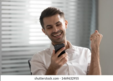 Excited male hold smartphone laugh triumph win lottery or application game online, overjoyed man worker feel euphoric happy get pleasant message on cellphone, read good news on cellular