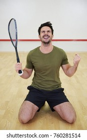 Excited male squash player celebrating on court