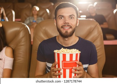 Excited male viewer keeping popcorn in hands and watching interesting film in cinema. Young bearded man wearing shirt expecting final of movie. Concept of entertainment and leisure.