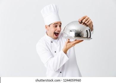 Excited man chef cook wearing uniform opening cloche cover isolated over white background