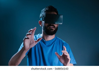 Excited man experiencing virtual reality via VR headset and touching something with his hands
