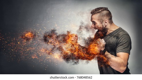 Excited man in fighting gesture with fists on fire. Rage concept. Heated fight. Aggressive behaviour concept