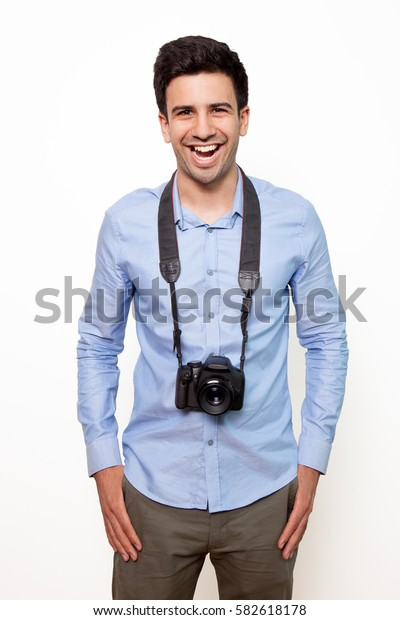 Excited man with hanging camera in studio