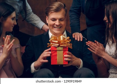 Excited man holding a birthday present from his friends at the birthday party. Smiling young man in suit sits on a couch and holds his gift for the birthday - a red box with golden ribbon. Close up