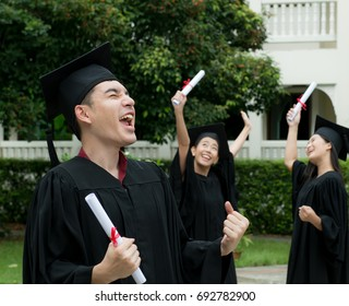 Excited a man jumping in their graduation,Happy Asian man and women in graduation gowns holding, Education,Gesture and people concept - group of happy graduate in bachelor gowns with diplomas.