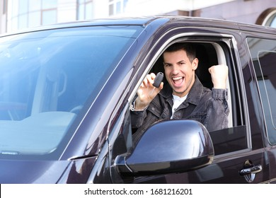 Excited man with key sitting in car outdoors. Buying new auto