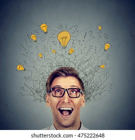 Excited man with many ideas light bulbs above head looking up isolated on gray wall background. Eureka creativity concept