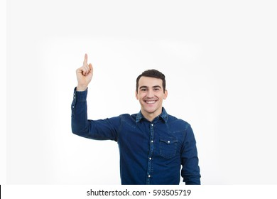 Excited man pointing up over white background.Smiling young man pointing up  with a new idea over white background.