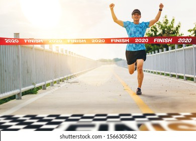Excited man runner crossing the 2020 finish line of marathon. 2020 success concept