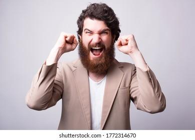 Der aufgeregte Mann schreit und macht die Gewinnergeste auf weißem Hintergrund.