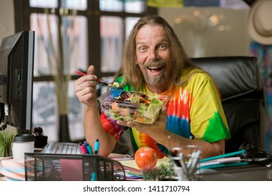 Excited man in tie dye shirt eating healthy food at his desk