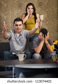 Excited man and woman with distraught son watching television
