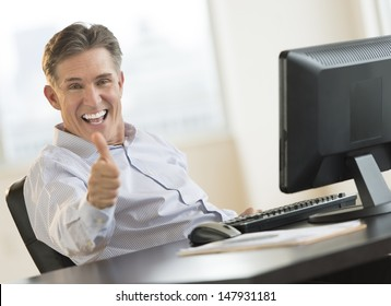 Excited mature businessman gesturing thumbs up while sitting at computer desk in office